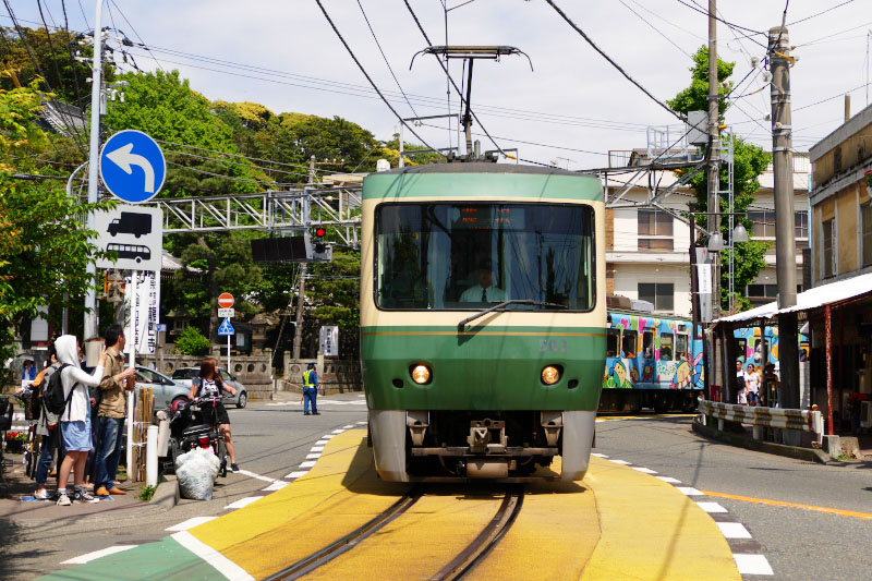 Enoden Line train runs street.