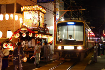 A Enoden train passing aside of illuminated festival floats.