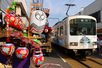 Train passing aside of colorful decorated festival float.