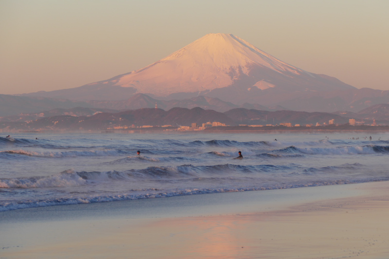 Snow-capped Mt.Fuji and surfers in winter morning.