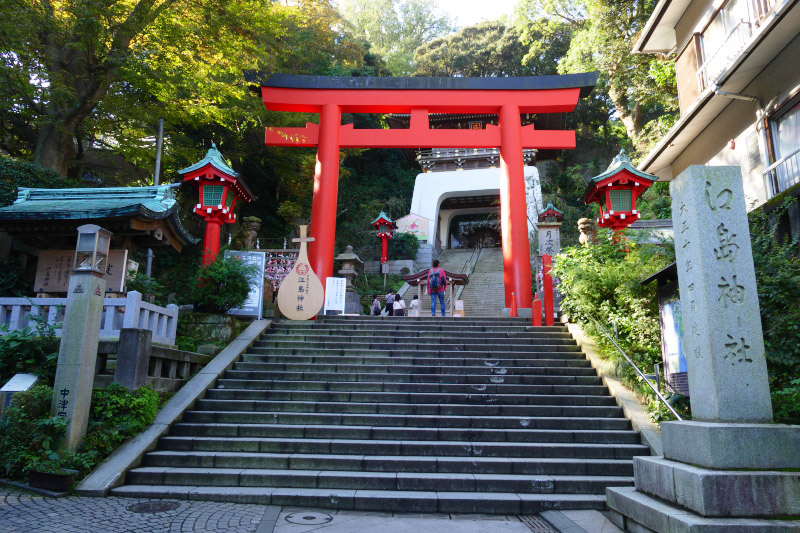Red torii gate stands at the boundary with the sanctuary and commercial area.